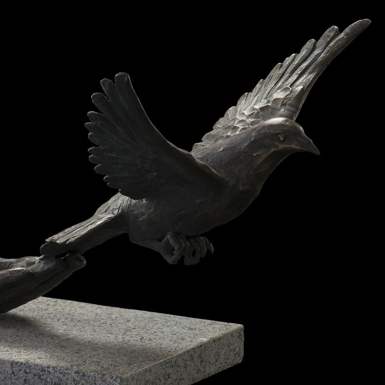 A cast bronze sculpture on a granite base by Brian Dean Christensen, depicting the Spirit of God descending like a dove.