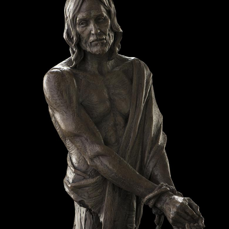 A bronze and sandstone sculpture by Benjamin Ray Hammond depicting the suffering Christ.